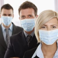 Business people fearing h1n1 swine flu virus wearing protective face mask and standing in a row