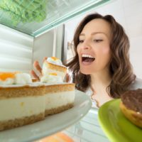 Hungry young woman choosing slice of cake as comfort food from the fridge