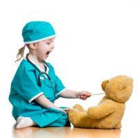 Child pracitcing safely feeding medicine to her teddy bear